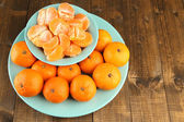 Ripe tangerines in bowl on wooden background — Stock Photo