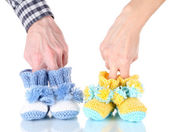 Hands with crocheted booties for baby, isolated on white — Stock Photo