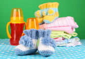 Composition with crocheted booties for baby, clothes and other things on color background — Stock Photo