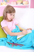 Little girl draws sitting on sofa in room — Stock Photo