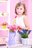 Little girl sitting on small ladder with flowers on pink background — Stok fotoğraf