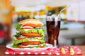 Huge burger on color plate and glass of cold drink, on bright background — Stock Photo