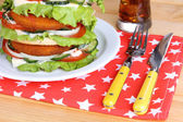 Huge burger on color plate and glass of cold drink, on wooden background — Stock Photo