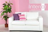 Vit soffa i rum på rosa vägg bakgrund — Stockfoto