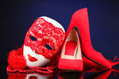 Beautiful red female shoes and carnival mask, on blue background — Stock Photo
