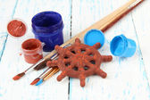Hand made ceramic wheel and color paints on wooden table — Stock Photo