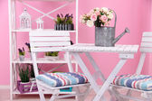 Garden chairs and table with flowers on shelves on pink background — Stockfoto