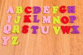 Alfabeto inglés sobre fondo de madera — Foto de Stock