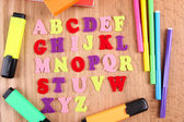 English alphabet, books and markers on wooden background — Stock Photo