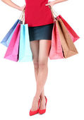 Female in red shoes holding shopping bags isolated on white — Stock Photo