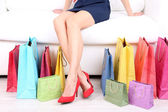 Female in red shoes sitting on sofa with shopping bags close up — Stock Photo