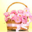 Stock Photo: Bouquet of eustomflowers in basket, on yellow background