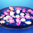 Rose petals and candles in water in vase on blue background close-up — Stock Photo #39278325