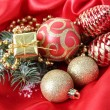 Beautiful Christmas decor on red satin cloth — Stock Photo #39278739