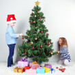 Kids decorating Christmas tree with baubles in room — Stock Photo #39279573