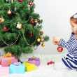 Little girl decorating Christmas tree with baubles in room — Стоковое фото