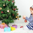 Little girl decorating Christmas tree with baubles in room — Stock Photo