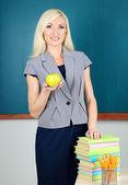 School teacher with apple on blackboard background — Stock Photo