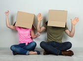 Couple with cardboard boxes on their heads sitting on floor near wall — Stockfoto