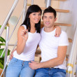 Young couple with keys to your new home on staircase background — Stock Photo