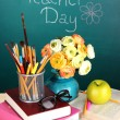 School supplies and flowers on blackboard background with inscription Teacher Day — Stock Photo #39280539