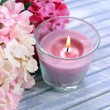 Stock Photo: Beautiful colorful candles and flower,on color wooden background