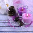 Stock Photo: Beautiful colorful candles and orchid flowers, on color wooden background