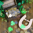 Chest with coins and horseshoe on wooden table close-up — Stock Photo #39281361