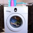Stock Photo: Washing machine loaded with clothes in bathroom