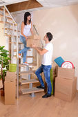 Young couple with boxes in new home on staircase background — 图库照片