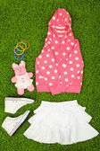 Beautiful clothes for little girl on green carpet — Stock Photo
