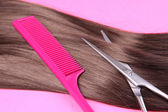 Long brown hair with comb and scissors on pink background — Foto de Stock