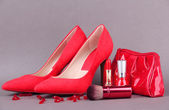 Beautiful red female shoes and cosmetics, on grey background — Stock Photo