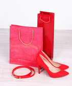 Beautiful red female shoes, belt and shop bags — Foto de Stock