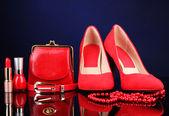 Belle rossi femminile accessori e cosmetici, su sfondo blu — Foto Stock