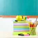 School supplies on table on blackboard background — Stock Photo