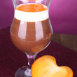 Stock Photo: Dessert of chocolate and persimmon on table on purple background