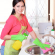 Beautiful young womcleans in kitchen — Stock Photo #39435415