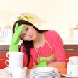 Beautiful young woman wipes clean utensils in kitchen — Stock Photo #39435433