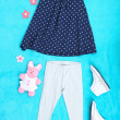 Beautiful clothes for little girl on blue background — Stock Photo #39436711