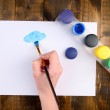 Hand holding brush with paints and paper on wooden background — Stock Photo