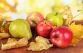 Beautiful ripe apples and pear with yellow leaves on table on bright background — Stock Photo
