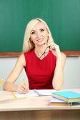 Blackboard zemin üzerine masada oturan öğretmen — Stok fotoğraf