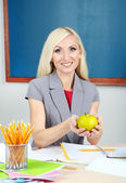 School teacher with apple sitting at table on blackboard background — Stock Photo