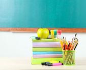 School supplies on table on blackboard background — Photo