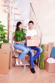 Young couple with boxes in new home on staircase background — Stok fotoğraf