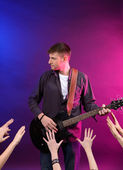 Guitarist singing on stage at a rock concert for his adoring fans — Stock Photo