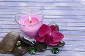 Prachtige kleurrijke kaarsen en orchideebloem, op een houten achtergrond kleur — Stockfoto