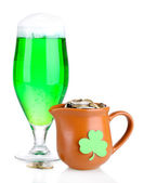 Glass of green beer and pitcher with coins isolated on white — Stock Photo