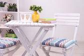 庭の椅子とテーブルに白い背景の上の棚の上の花 — ストック写真